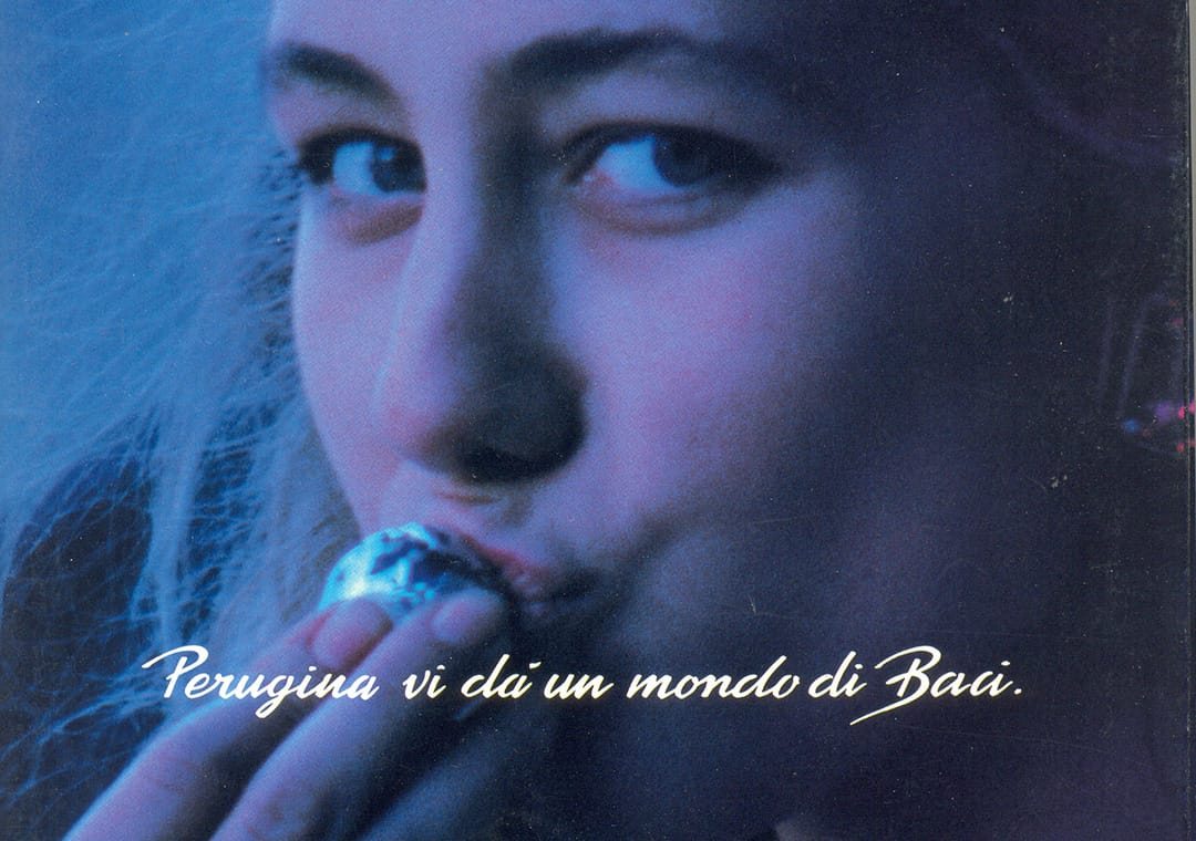 Advertising of blond girl kissing Baci Perugina chocolate