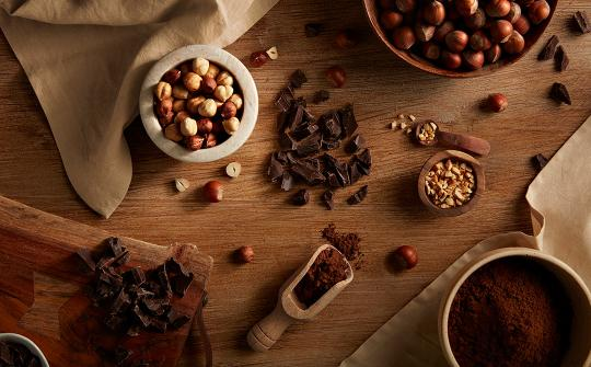 Chocolate, hazelnuts and cocoa scattered on the table